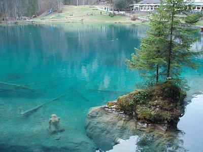 Blauensee - Blauensee je krásná podívaná na průzračně modrozelené jezero. Kolem dokola jsou hory. Je to krásná romantická podívaná. Navíc nese svou historii. Na fotografii je znázorněna žena pod hladinou, ta nese povídku o tomto jezeře. (nahrál: monika)